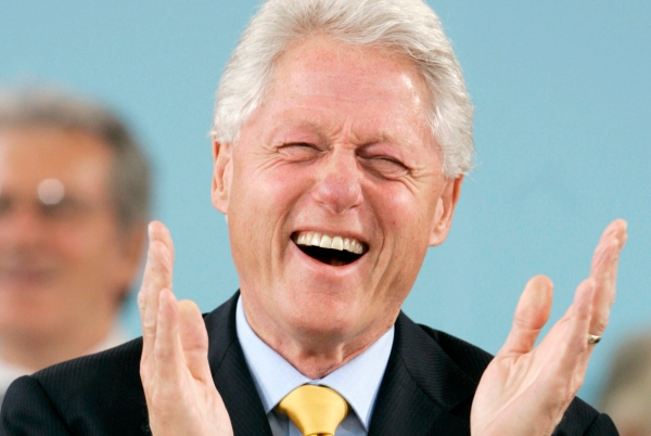 Former U.S. President Clinton laughs during the student speeches in Cambridge
